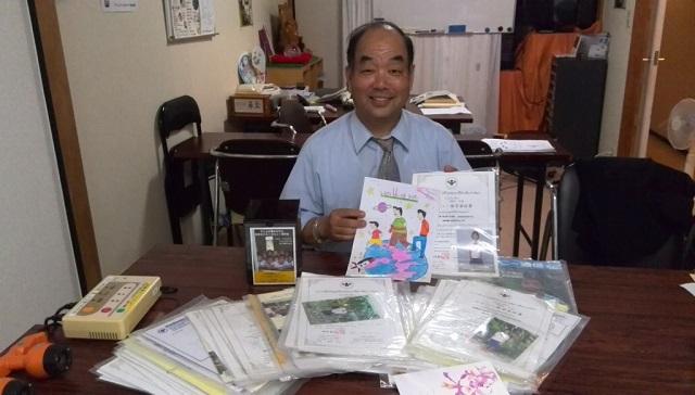 10年間分の奨学生写真と報告書を掲げる末松社長
