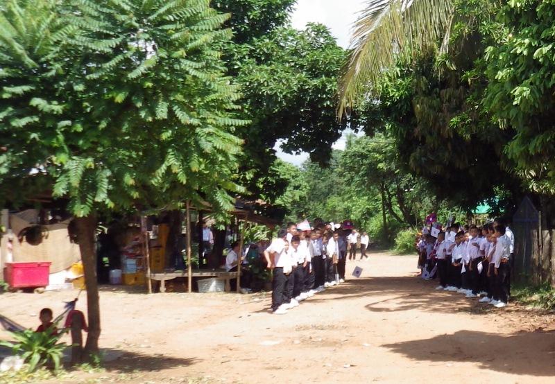 旗を持って出迎えるラオス児童たち