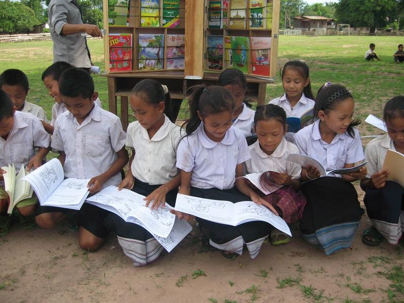図書ボックスの本を読むラオスの子ども達の様子